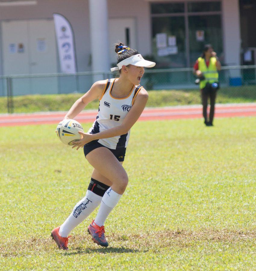 Bianca+T.+%28%E2%80%9819%29+wears+a+knee+brace+on+her+left+leg+as+she+passes+the+ball+during+an%0AIASAS+touch+rugby+game.+%5BPhoto+courtesy+of+International+School+of+Kuala+Lumpur%5D